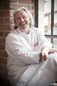 Der Gastronom Bernhard Reiser sitzt lachend am Fenster